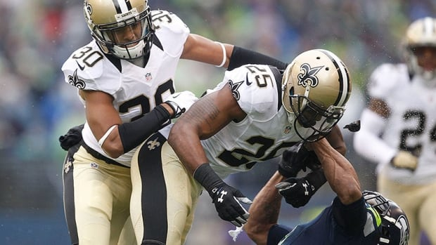 Saints' safety Rafael Bush, centre, lays out Seahawks' wide receiver Percy Harvin, right, in an NFC divisional playoff on Jan. 11, 2014.