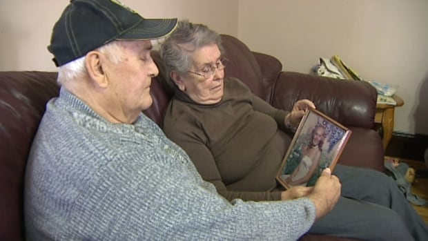 The Camerons hold a photo of their granddaughter.