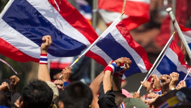 Anti-government protesters clench their fists during a rally outside Thai police headquarters, Saturday, Jan. 18, 2014 in Bangkok, Thailand.