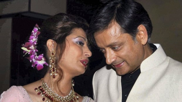 Former Indian Junior Foreign Minister Shashi Tharoor listens to his wife Sunanda Pushkar at their wedding reception in New Delhi, India.