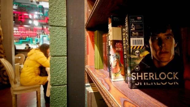 "A girl has a drink near books shelf displaying Sherlock Holmes books at a ""Sherlock""-themed cafe in Shanghai, China."