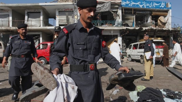 A soldier of Pakistani para military force collects the belongings of his colleagues after a bombing in Shabqadar near Peshawar, Pakistan on Friday, May 13, 2011.