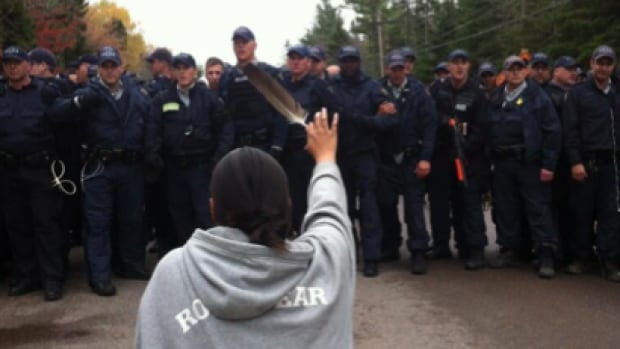 A woman kneels in front of a line of police officers while protesting fracking in Elsipogtog, N.B., on Oct. 17, 2013.