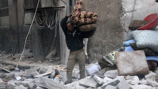 A resident collects belongings amid debris after an air strike in Aleppo, Syria on Sunday. The United Nations says Iran has been invited to attend a meeting of foreign ministers In Switzerland ahead of internationally brokered peace talks between Syria's warring factions.