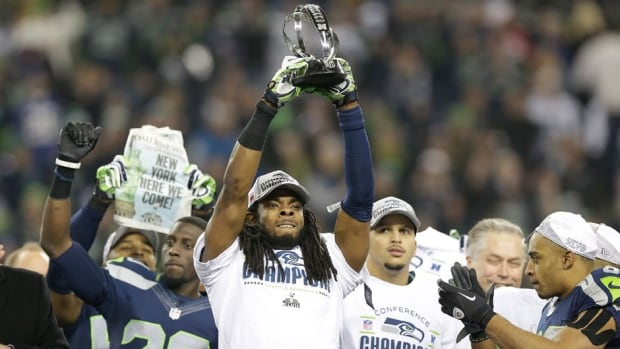 Seahawks cornerback Richard Sherman holds up the George Halas Trophy after winning the NFC Championship game against the San Francisco 49ers on Sunday in Seattle.