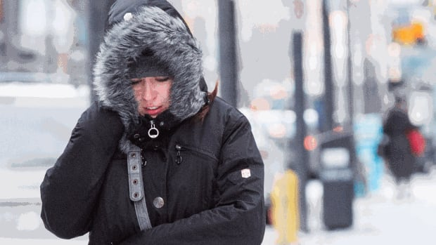 A woman braves the cold on King Street near University in Toronto earlier this month. Temperatures are forecast to fall overnight Monday, bringing lows in the -20 C range. (Katherine Holland/CBC)