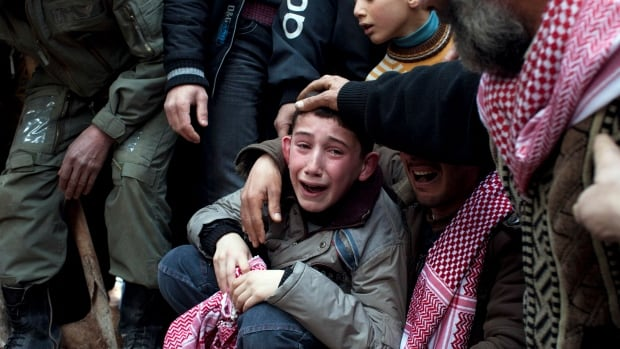 Ahmed, centre, mourns his father who was killed by a Syrian Army sniper. Diplomats and political leaders planning an upcoming peace conference acknowledge that a quick end is unlikely for a conflict that has killed more than 130,000 people.