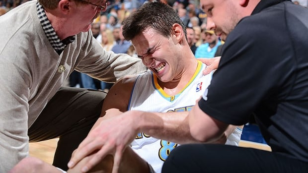Nuggets small forward Danilo Gallinari is surrounded by trainers as he clutches his knee in pain after tearing his ACL. He will miss the balance of the NBA season after suffering a setback.