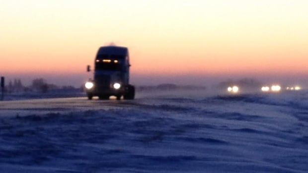 The sun rises on a cold, blustery day in Manitoba, as traffic makes its way along the Trans-Canada Highway near Winnipeg.