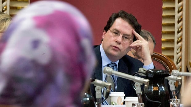 The Quebec minister responsible for the secular charter, Bernard Drainville, listens to Samira Laouni at public hearings that began Jan. 14. The government is not willing to change the main thrust of the bill, he announced.