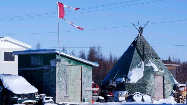 A shredded Canadian flag flies over a building in Attawapiskat, Ont., in November 2011. The First Nation has been making progress in its accounting, but a 2012-13 clerical error in its financial statements went unnoticed by both Ottawa and the band's auditing firm.