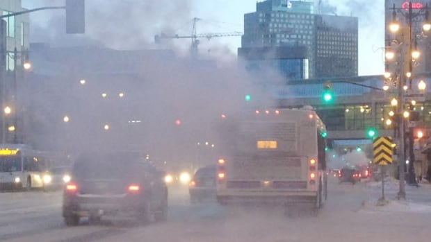 Exhaust fog fills the air on Portage Avenue on a cold Thursday morning in Winnipeg.