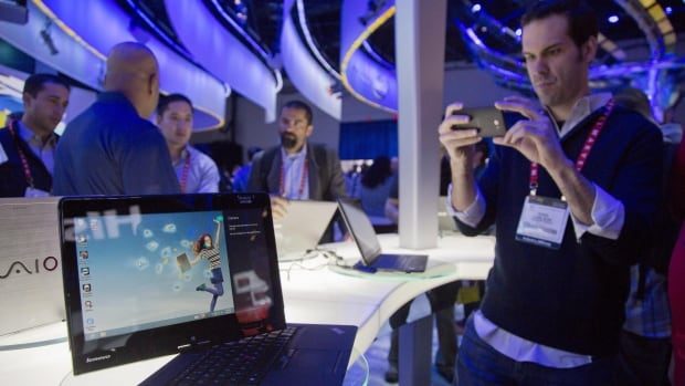 Convention goers photograph a Lenovo convertible Ultrabook at the Consumer Electronics Show on Jan. 8, 2013. Already the world's biggest PC maker, Lenovo has bought IBM's server business.