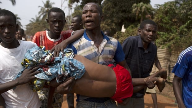 Men carry a boy, who died shortly after from a gunshot wound, during a violent confrontation between Muslims and Christians in the Central African Republic on Friday. At least 50 Muslims have been killed.