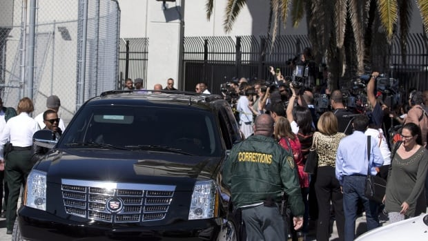 Members of the media and fans surround the motorcade as they wait for pop singer Justin Bieber to be released from jail Thursday in Miami. Police who escorted Bieber several days earlier from the airport were suspended Friday.