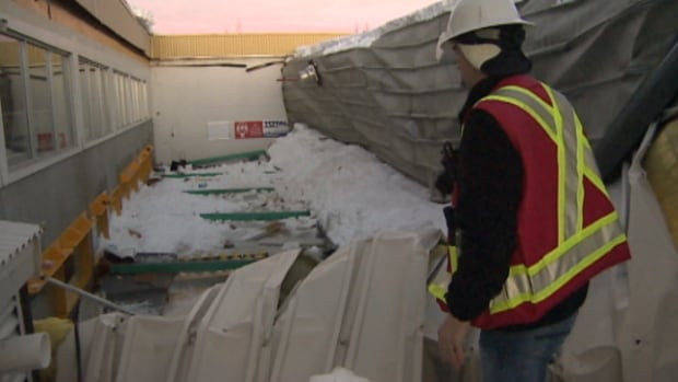 A worker examines the portion of the Omniplex curling rink roof that collapsed on Friday afternoon
