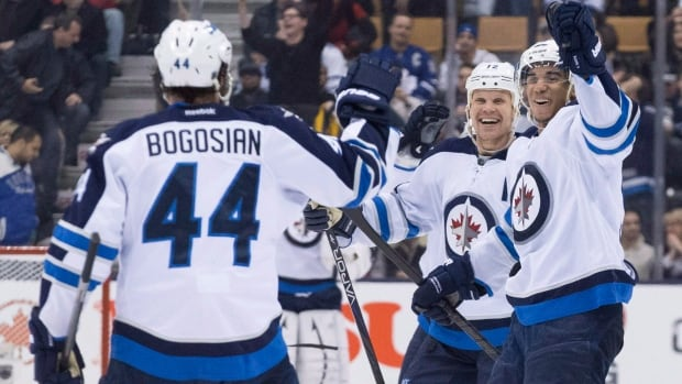 Winnipeg Jets' Evander Kane (right) and Olli Jokinen congratulate Zach Bogosian (left) after he scored the winning goal against Toronto Maple Leafs in shoot out NHL hockey action in Toronto on Saturday March 16, 2013.THE CANADIAN PRESS/Chris Young