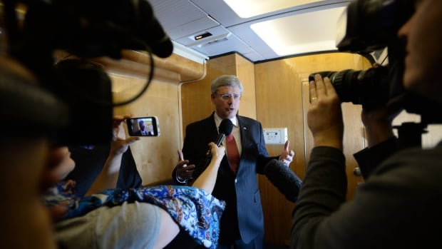 Prime Minister Stephen Harper delivers a statement while aboard Royal Canadian Air Force 001 on route from Amman, Jordan to Ottawa on Saturday, January 25, 2014. Harper's former spokesman says political staffers have to talk to journalists more and rely on email a lot less.