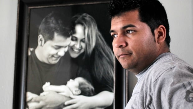 Erick Munoz stands with an undated copy of a photograph of himself, left, with wife Marlise and their son Mateo, in Haltom City, Texas. , File)