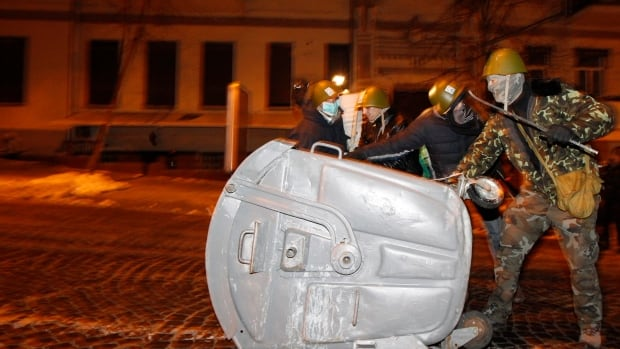 Anti-government protesters use trash container to build a barricade at the Ministry of Justice in central Kyiv Monday. MPs in Ottawa voted to pass a motion condemning the Ukrainian government's use of violence against protesters.