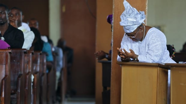 A woman prays during a New Year's day service at the Holy Rosary Catholic Church in Abuja on Jan. 1, 2014. Churches are often a target in Nigeria's sectarian violence aimed at Christians.