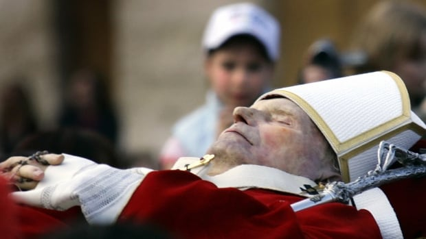 A young boy looks at the late Pope John Paul II during a procession at Saint Peter's square at the Vatican in April 2005. Thieves have stolen a container of the late pope's blood from a church in Italy.