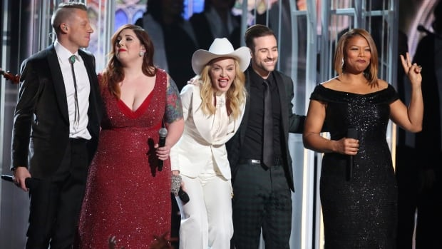 Performers (from left) Macklemore, Mary Lambert, Madonna, Ryan Lewis and Queen Latifah appear on stage during a performance of Same Love and a wedding for 33 couples at the Grammy Awards on Sunday in Los Angeles.