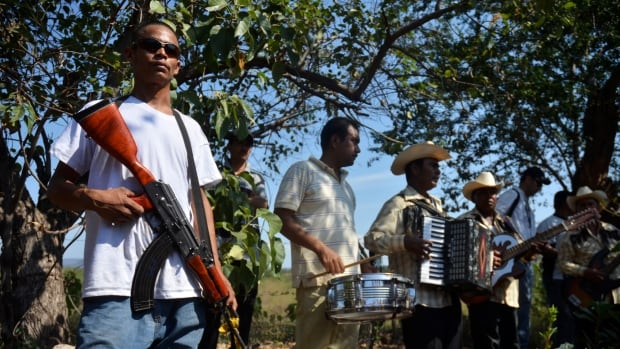 A vigilante stands next to a band during a funeral on January 15, 2014. Mexican vigilantes have been battling the Knights Templar cartel in the western state of Michoacan for almost a year.