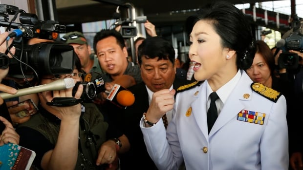 Thailand's Prime Minister Yingluck Shinawatra speaks to media as she leaves a meeting with election commissioners at the Army Club, Tuesday, Jan. 28, 2014, in Bangkok.  The government announced Tuesday it will go ahead with an election this weekend despite months of street protests and an opposition boycott.