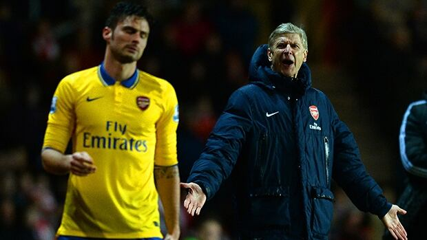 Arsene Wenger manager of Arsenal reacts as he looks at his player Olivier Giroud at St Mary's Stadium on January 28, 2014 in Southampton, England.