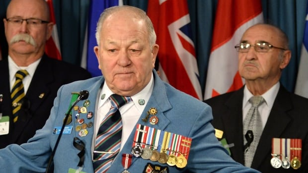 Veteran Ron Clarke joins fellow Veterans and PSAC members as they hold a news conference on Parliament Hill in Ottawa on Tuesday, Jan. 28. The group is asking ask the government to reconsider its decision to close Veterans Affairs district offices in nine communities.