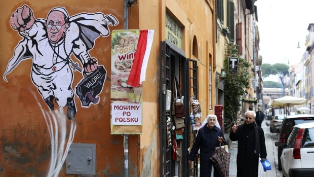 A priest and a nun walk by a large drawing of Pope Francis depicting him as a superhero on a wall near the Vatican on January 29, 2014. The Argentinian Pope is shown taking off into air with his right fist clenched in a classic Superman style.