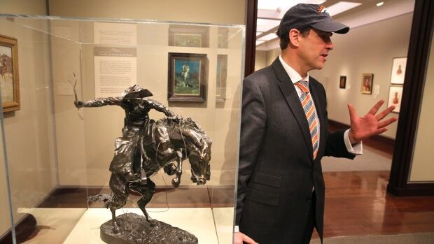 Denver Art Museum director Christoph Heinrich poses next to a Frederic Remington bronze of a cowboy riding a bucking horse, part of the museum's collection. The Denver and Seattle Art Museums have started a friendly wager: if the Broncos win the Super Bowl against the Seahawks, Seattle will send a Seahawk mask to Denver for three months. If the Seahawks win, Denver sends the Remington statue to Seattle for three months.