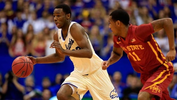 Andrew Wiggins, left, of the Kansas Jayhawks controls the ball as Monte Morris of the Iowa State Cyclones defends at Allen Fieldhouse on Wednesday in Lawrence, Kansas.