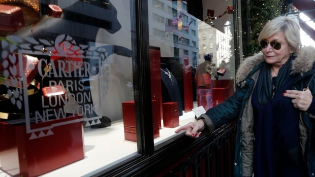 A woman window shops at the Cartier Store on 5th Avenue in New York where five masked men stole 17 watches in a daylight robbery.
