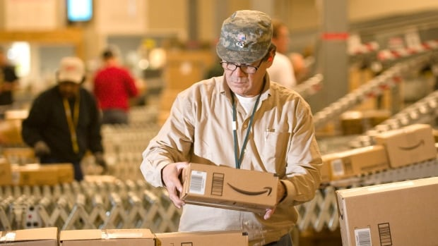An Amazon.com employee grabs boxes off the conveyor belt to load in a truck at their Fernley, Nev., warehouse. It had revenue of $25.59 billion in the fourth quarter of the year, but that was a disappointment to Wall Street.