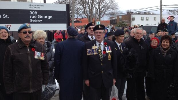 The crowd sings O Canada in Sydney in front of the veterans affairs office.