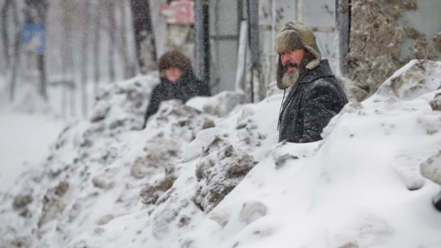 People wait in a snowed in bus stop during a blizzard in Bucharest, Romania, on Jan. 29, 2014. Weather forecasters issued a code red severe weather warning as a second wave of blizzards hit the southeastern regions of Romania disrupting road and rail traffic.