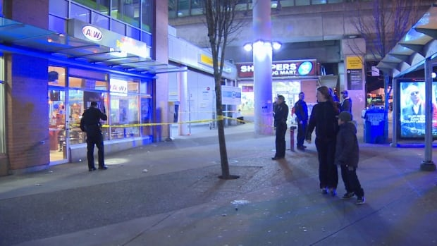 Vancouver Police officers look for evidence on the ground outside the Commercial-Broadway SkyTrain Station. A man was taken to hospital after being stabbed in what police believe was a targeted attack Friday night.