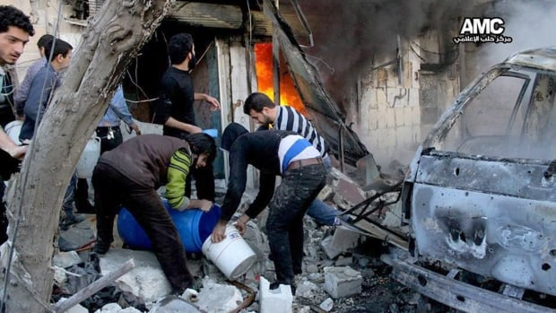 Syrians try to put out a fire caused by a government bomb in Aleppo on Saturday, Feb. 1.