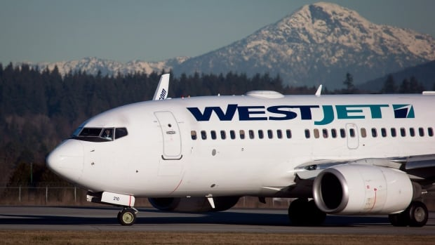 A pilot taxis a Westjet Boeing 737-700 plane to a gate after arriving at Vancouver International Airport in Richmond, B.C., on Monday February 3, 2014. WestJet posted strong traffic in May, an possible indication of a strong summer travel season.