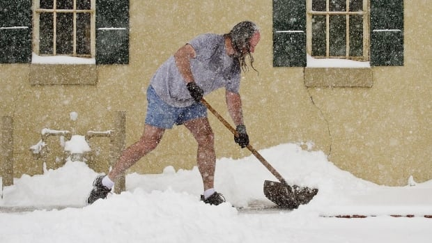 Troy Welty shovels snow in front of Mathew's Gallery in Wichita, Kan., on Tuesday  South-central Kansas is expecting up to 17 centimetres of snow as a winter storm passes through.