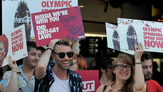 Pro-gay activists hold placards asking Sochi Winter Olympic sponsors to speak out against Russia's anti-gay laws during a protest under the iconic clocks of Flinders Street Railway Station in Melbourne on Feb. 5 2014.