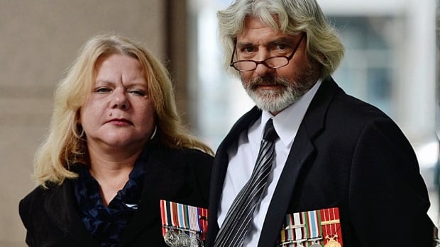 Veteran Lillian Frederiksen stands with her husband, veteran Michael Cole, who suffers from post-traumatic stress disorder, in Ottawa in December 2013 when former soldiers pleaded with the federal government to provide more support to veterans who are struggling to deal with the consequences of their military service.