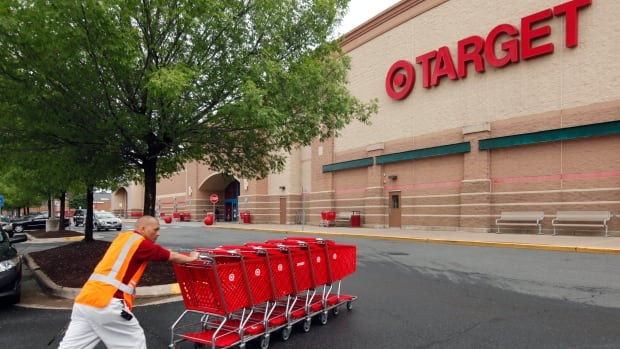 "Target is lowering its profit forecast, citing costs related to its huge data breach late last year and what it call a ""challenging"" retail environment."