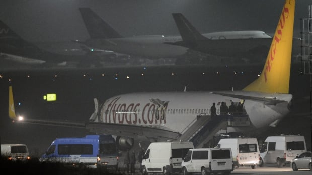 Turkish security officials enter the private Turkish company Pegasus plane before it was evacuated, at the Sabiha Gokcen Airport in Istanbul, Turkey, on Friday.