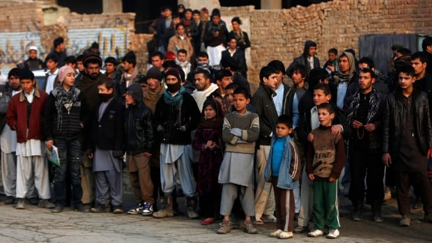 Afghans gather at the site of a suicide attack in Kabul January 26, 2014.  A UN report published on Saturday says 8,615 civilians were killed or injured last year in the country.