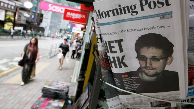 NSA leaker Edward Snowden is displayed on the front page of the South China Morning Post at a news stand in Hong Kong last year. According to a review by The Associated Press, several news organizations, including the CBC, have mistakenly disclosed sensitive details in their reports on the leaked NSA documents.