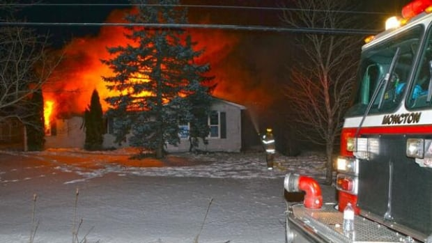 Firefighters battle a fire at the house which is fully engulfed in flames.