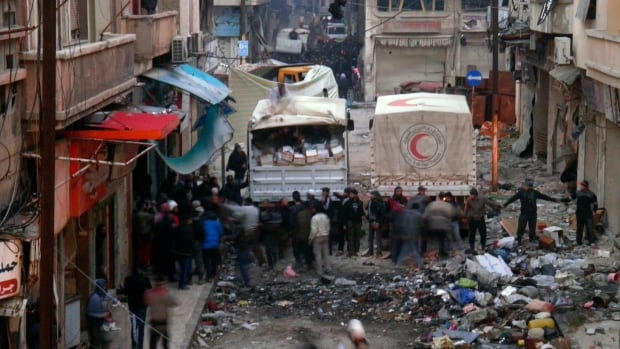 Red Crescent trucks stand by in the besieged neighbourhoods of Homs to supply humanitarian aid.